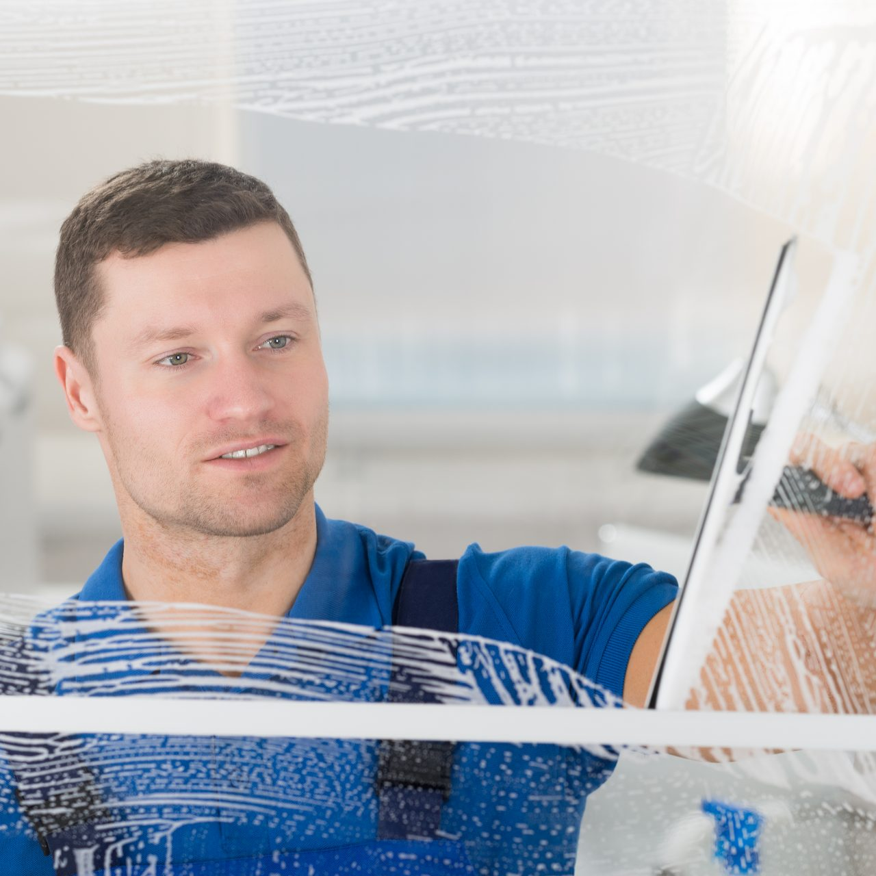 Smiling,Mid,Adult,Worker,Cleaning,Soap,Sud,On,Glass,Window